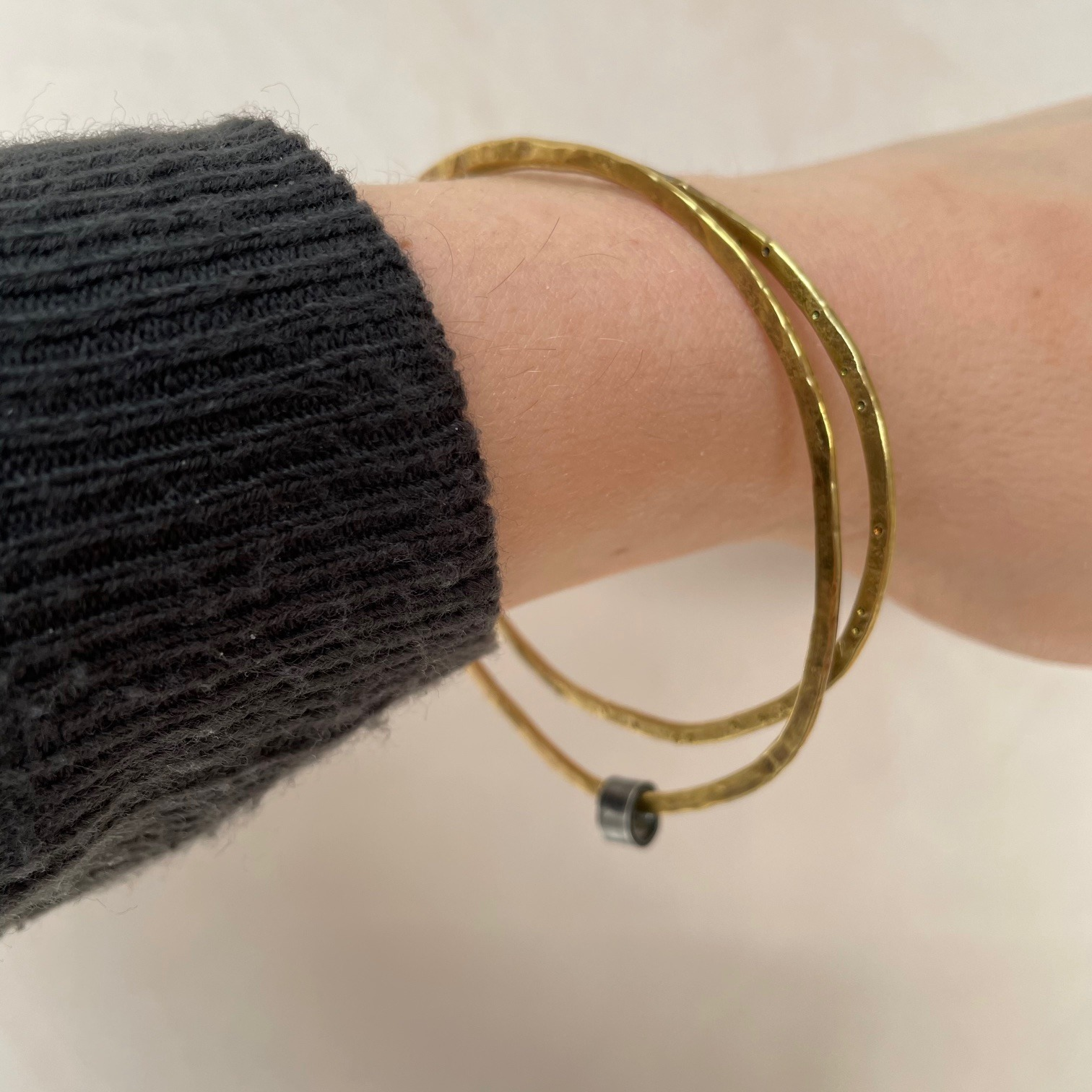 Hammered brass pebble shaped bangle by Sarah Drew
